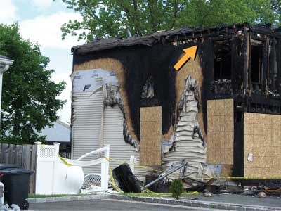 (9) The fire quickly and intensely progressed out the window and headed directly up to the eaves/soffits and entered the attic (arrow). (Photo by author.)