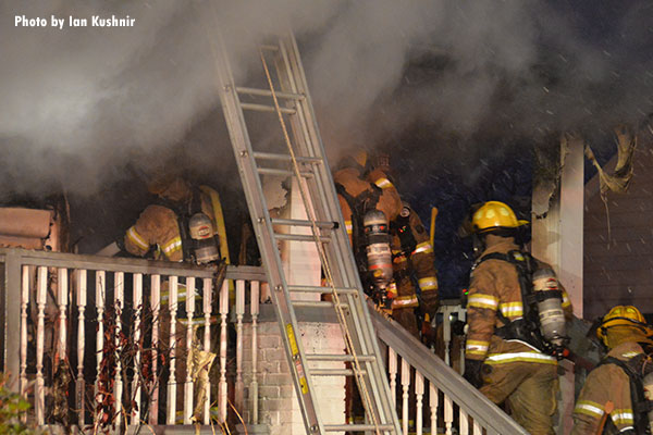 Firefighters operating on a porch during a Melvindale hosue fire.