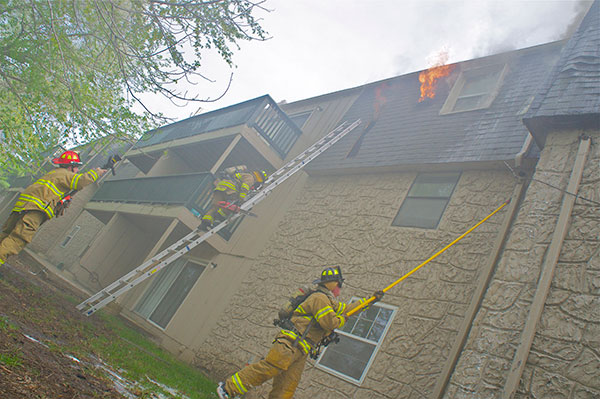 An exterior view of the second fire, as flames vent from the mansard roof of the apartment building.