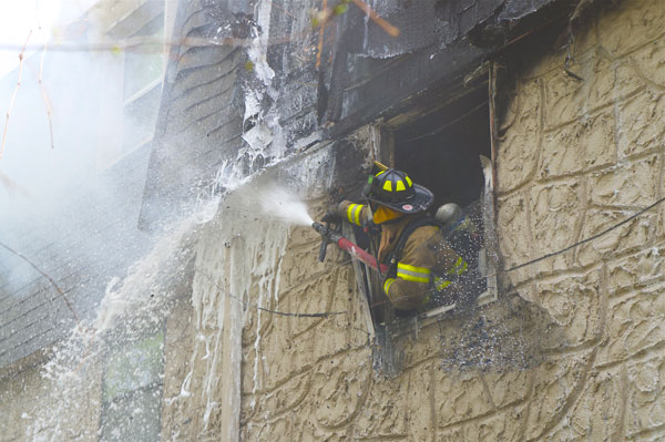 A firefighter trains a hose stream on fire in the second response.