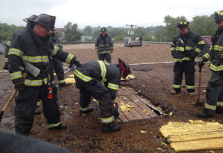 A senior firefighter shows new firefighters how critical it is to vent a metal deck roof without compromising the roof's structural integrity. (Photos by author.)