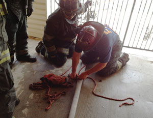Firefighters learn the proper rope technique to perform a rope stretch of a handline, demonstrated by the senior firefighter.