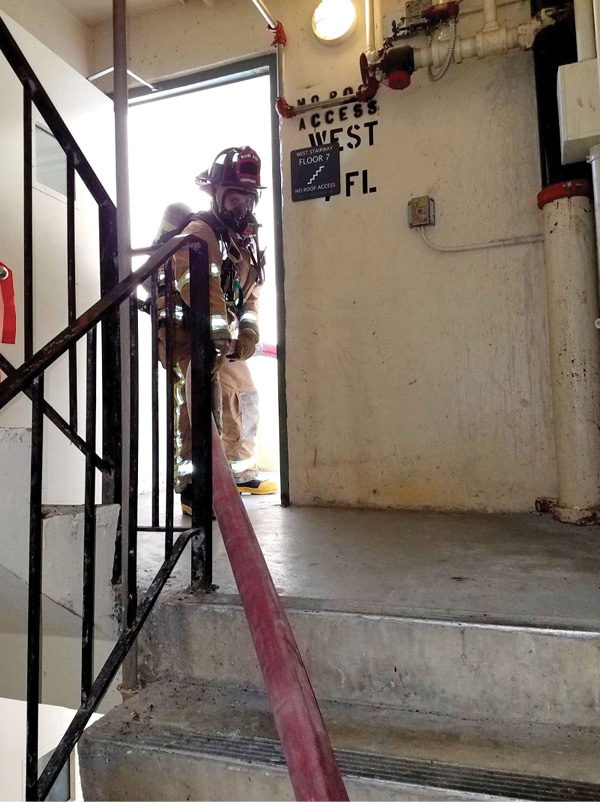 A firefighter positioned at the stairwell's fire floor landing feeds hose to the firefighters advancing the hoseline down the hallway.