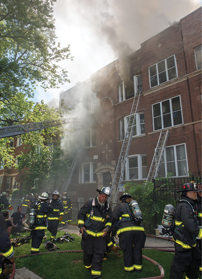 The front of the building as members are beginning offensive operations at an attached row type of private dwelling. (Photos by Gordon J. Nord Jr.)