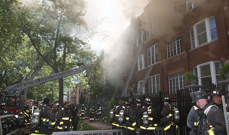 (2) On the front of the building, members placed portable ladders to the fire building and are now placing portable ladders to the top floor of the exposures on both sides. This will be a means for the members inside to evacuate in an emergency.