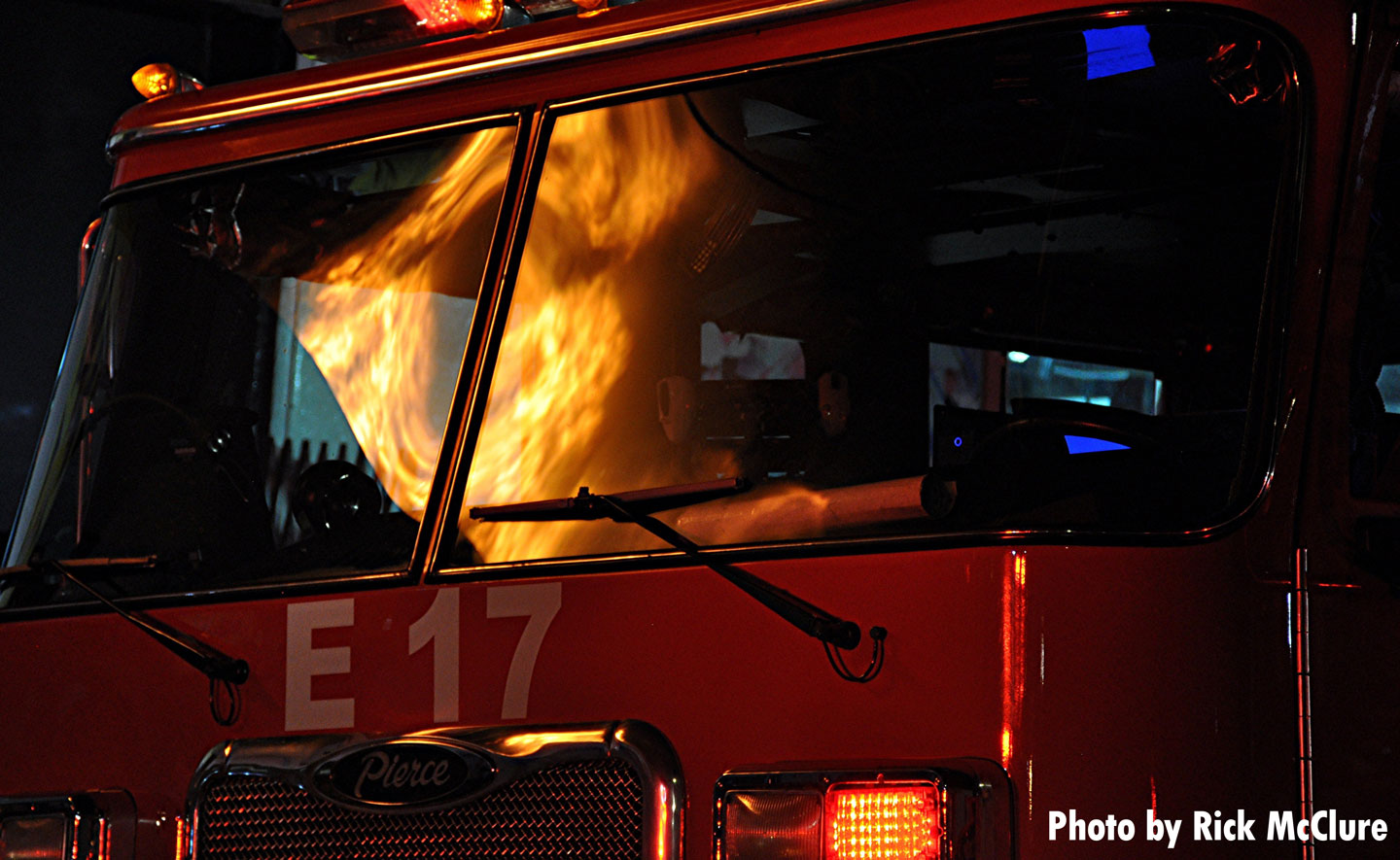 Fire reflected on the windshield of an apparatus.