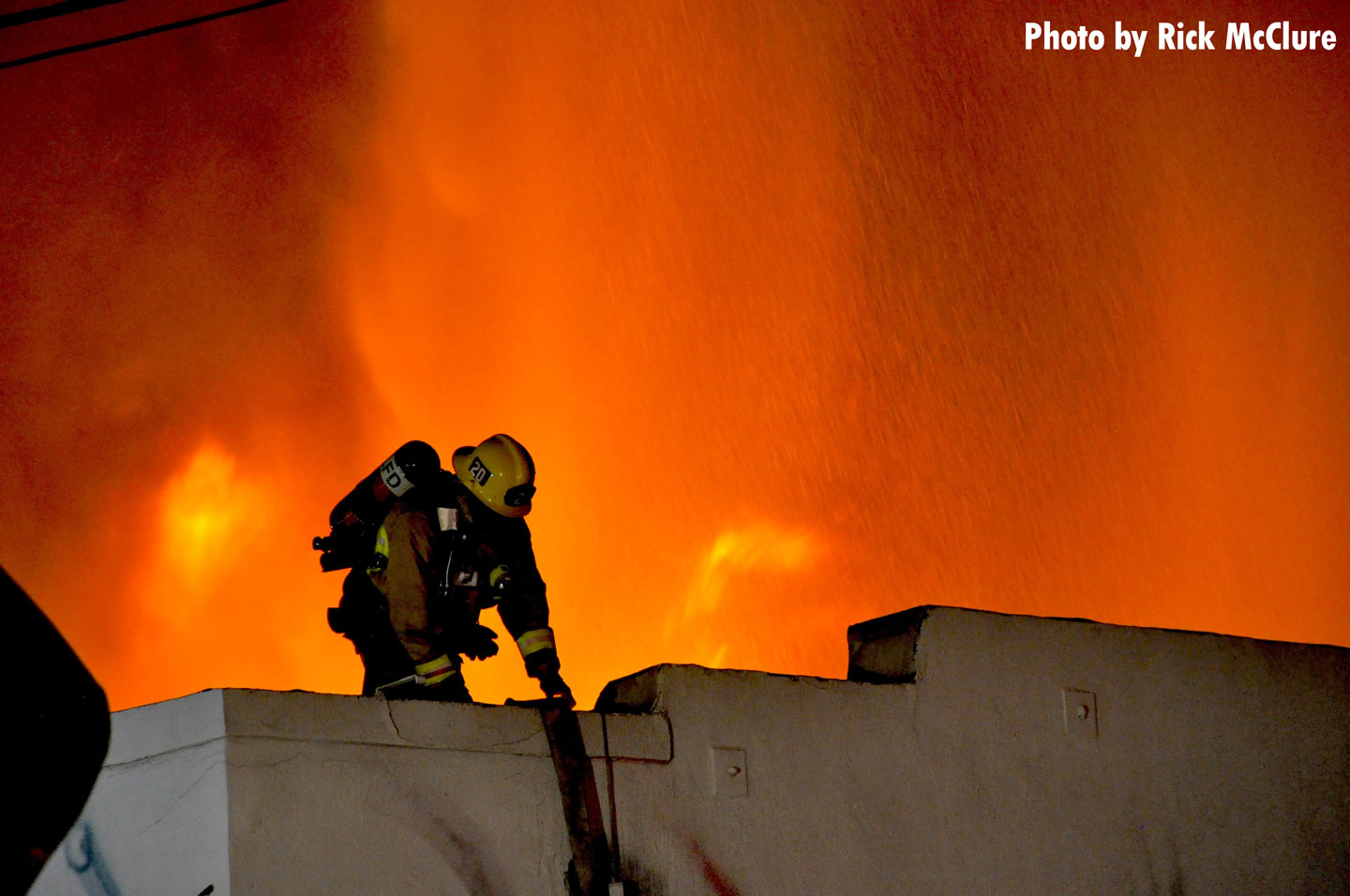 A firefighter on the roof of a structure with flames raging behind him.