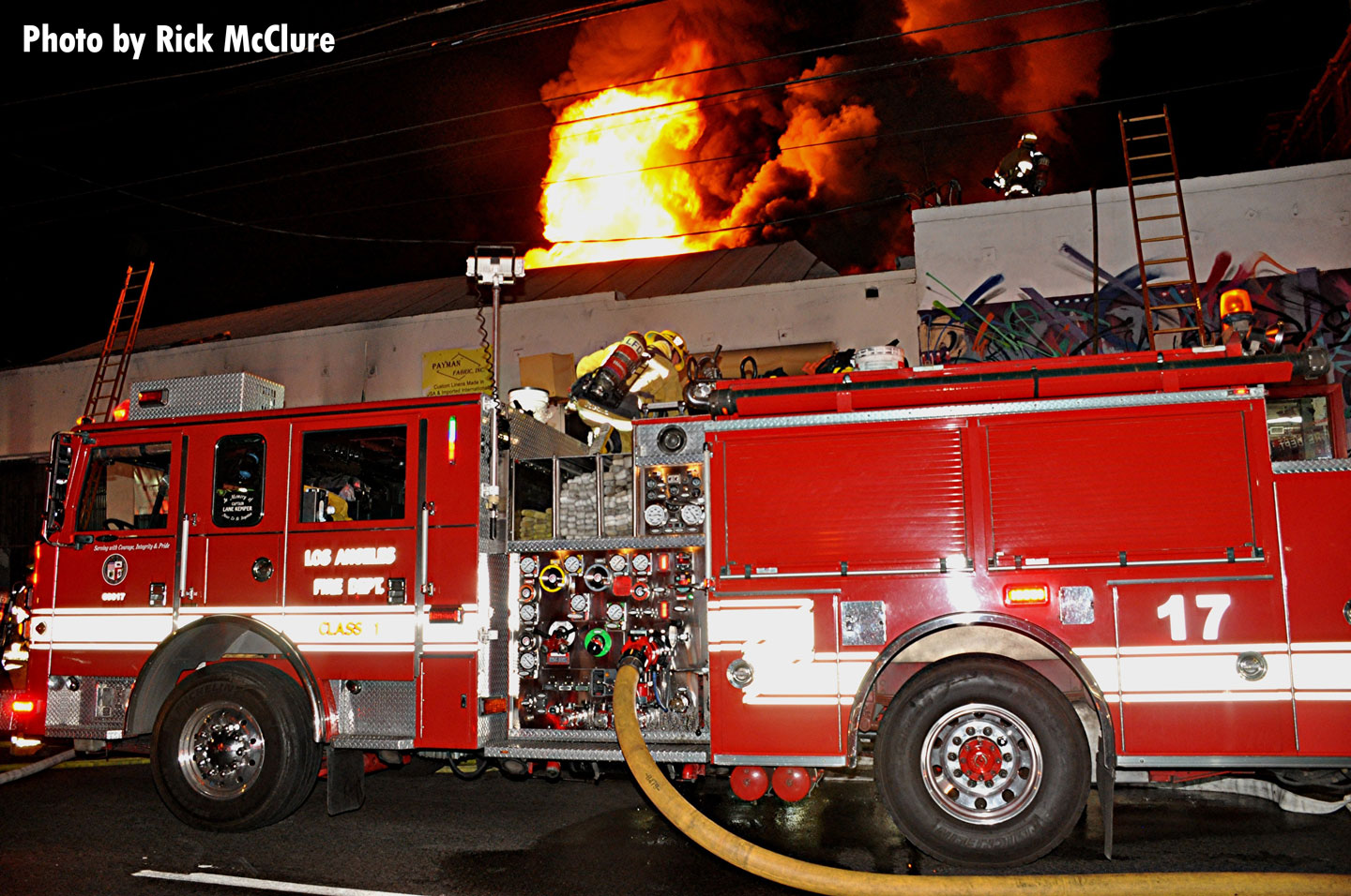Flames shoot through the roof of the building. An LAFD pumper in the foreground.