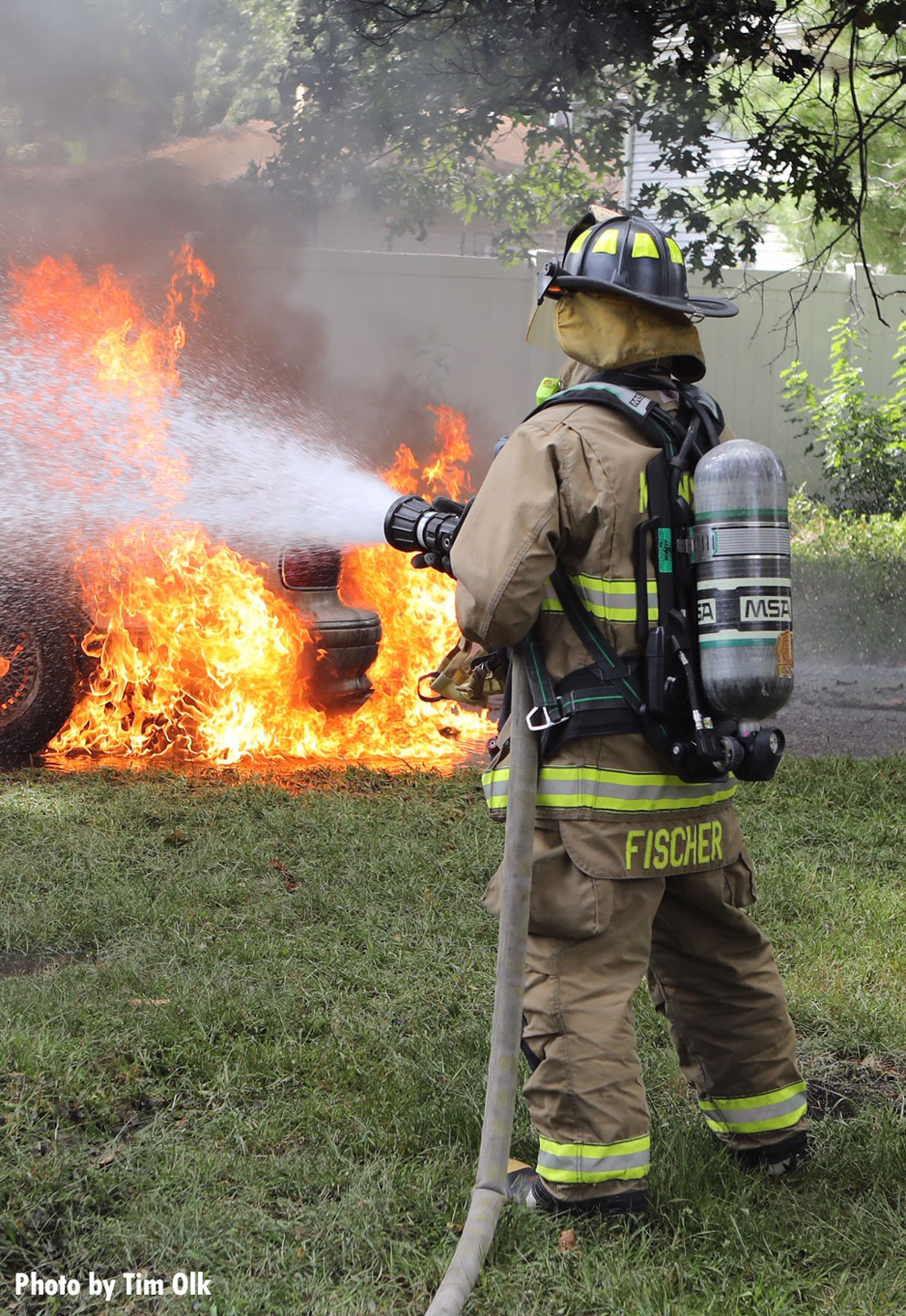 Another photo of a firefighter with a hoseline putting water on the fire.