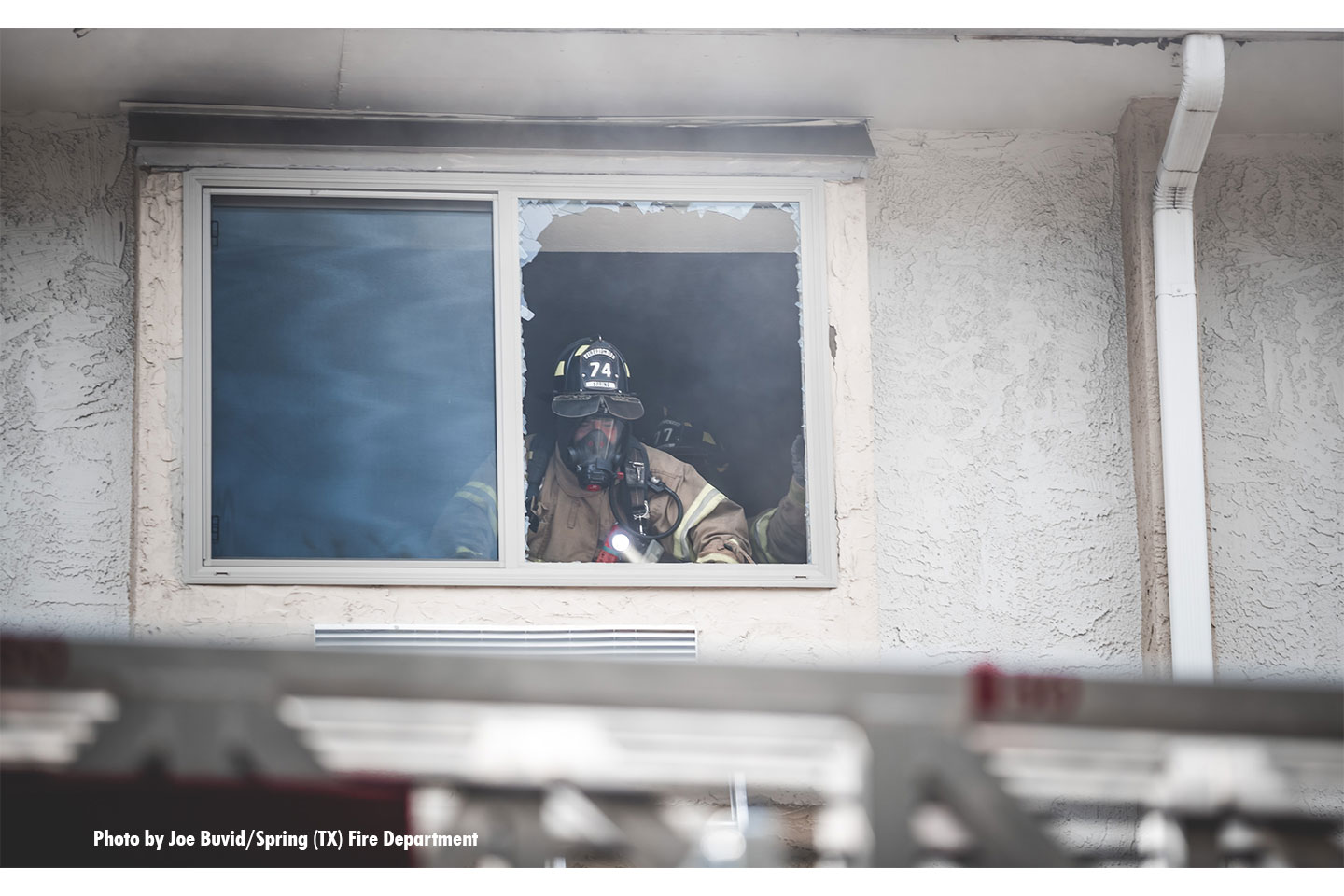 A firefighter inside the motel looks out on the scene.