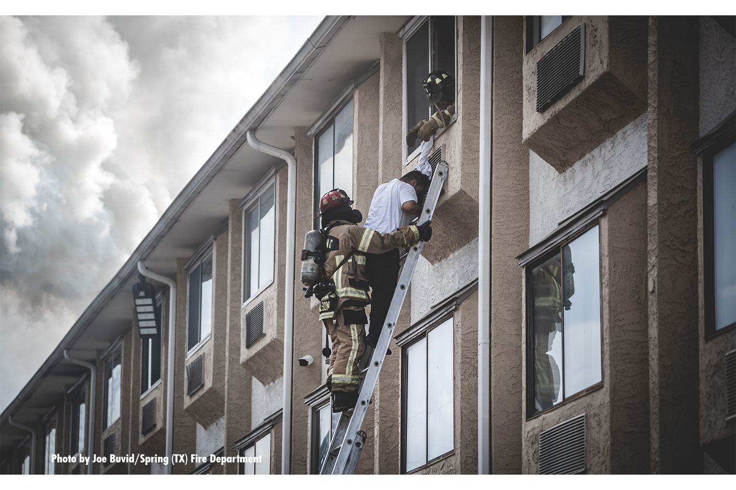 A firefighter assists a victim in a ladder rescue from a window.