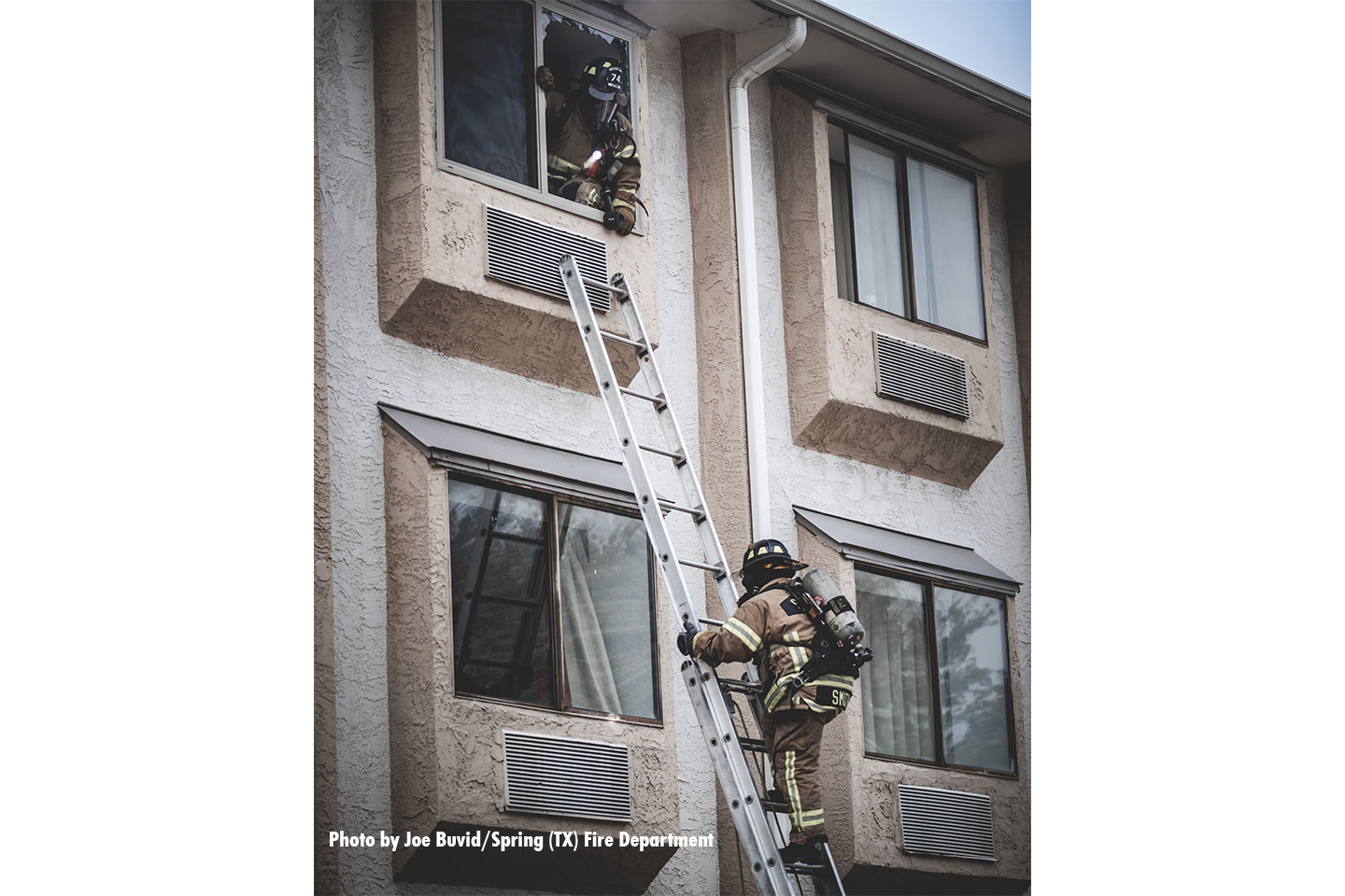 A firefighter on scene climbs a portable ladder.