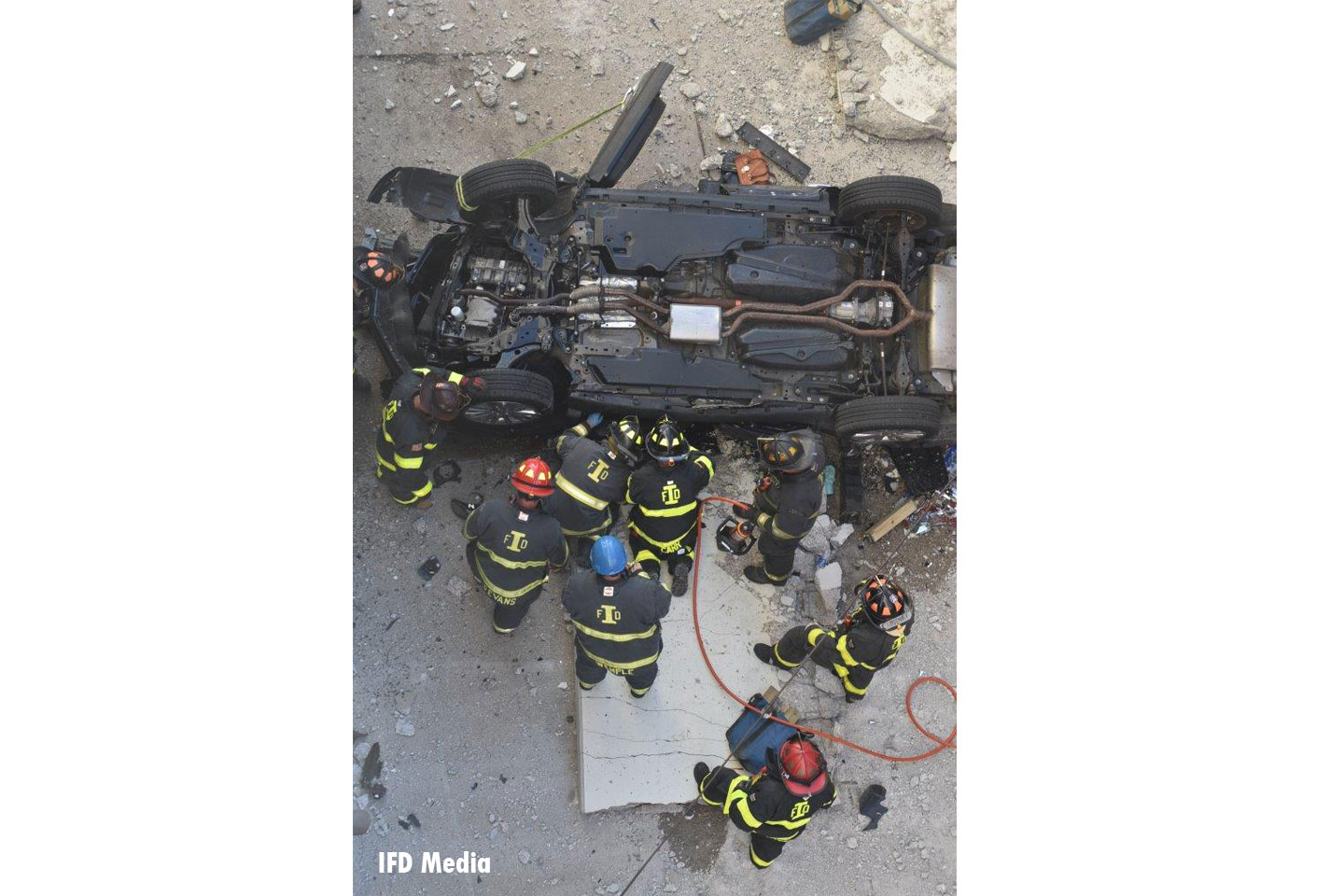 Firefighters work on the fallen vehicle.