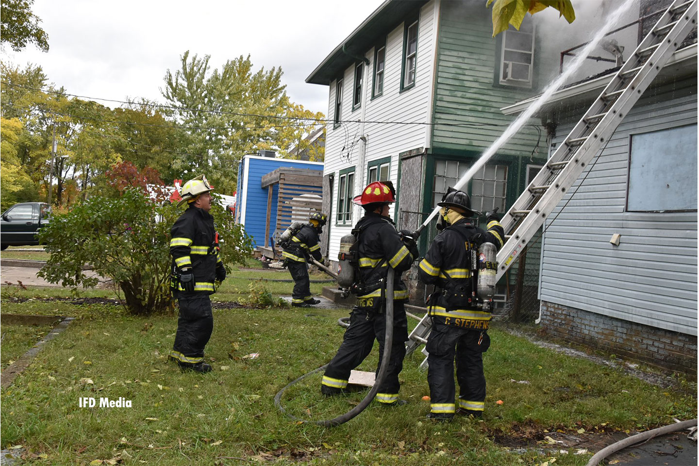 Firefighters operate a hoseline and a ladder at the fire.