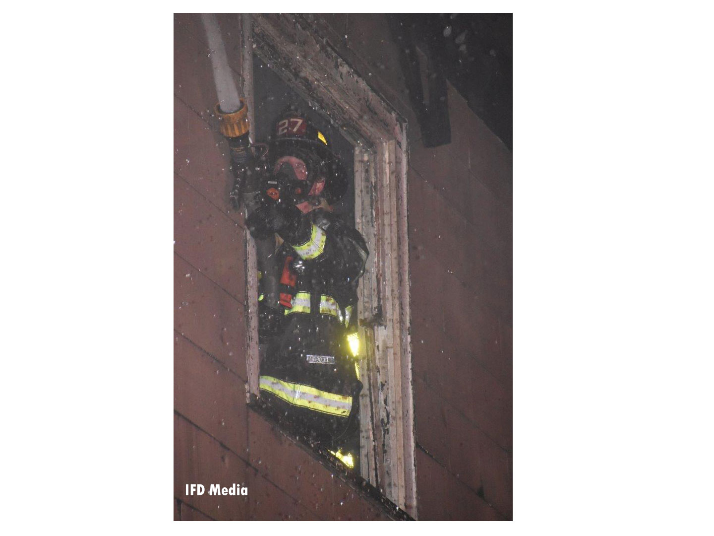 Firefighter with a nozzle in the window