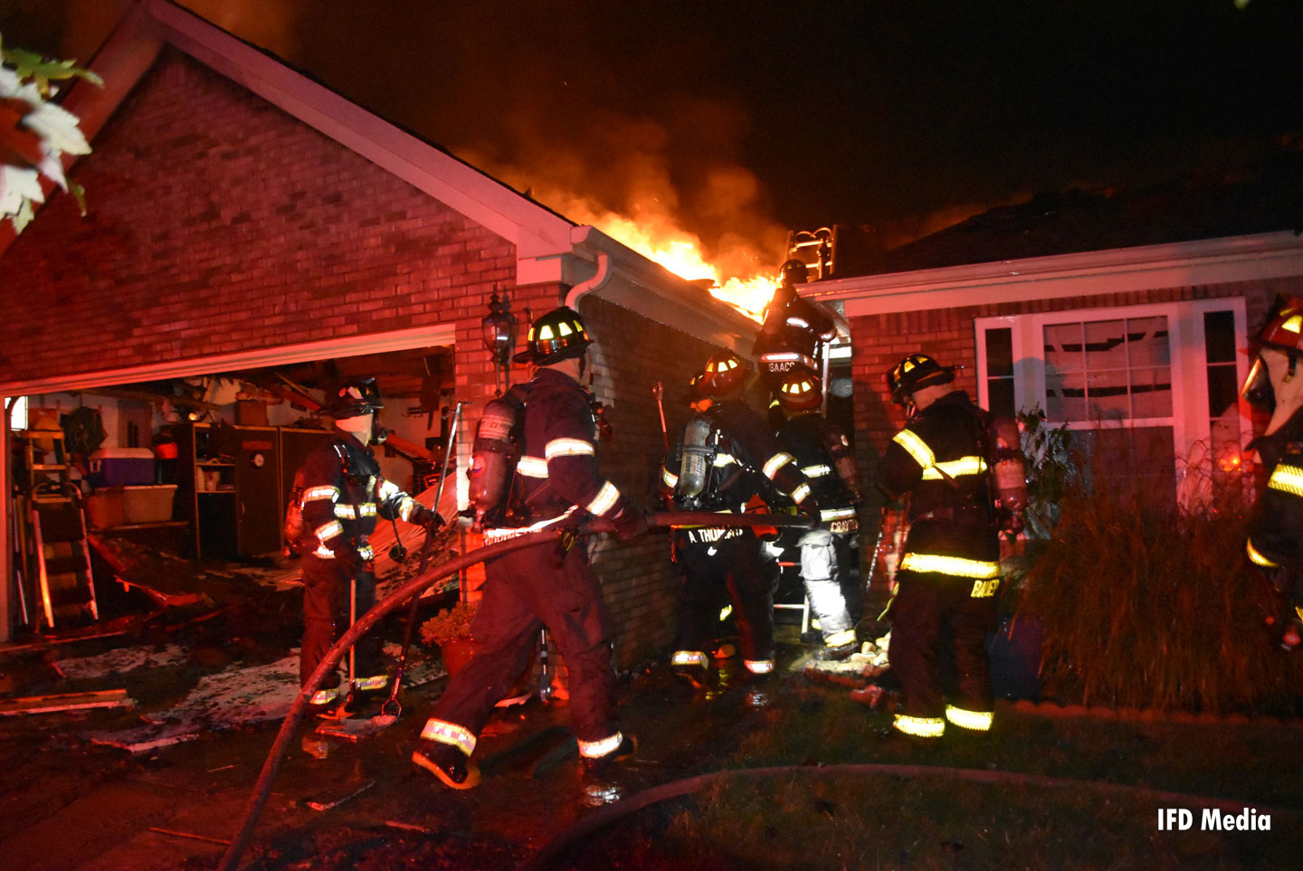Firefighters advance a hoseline to attack fire in a home.