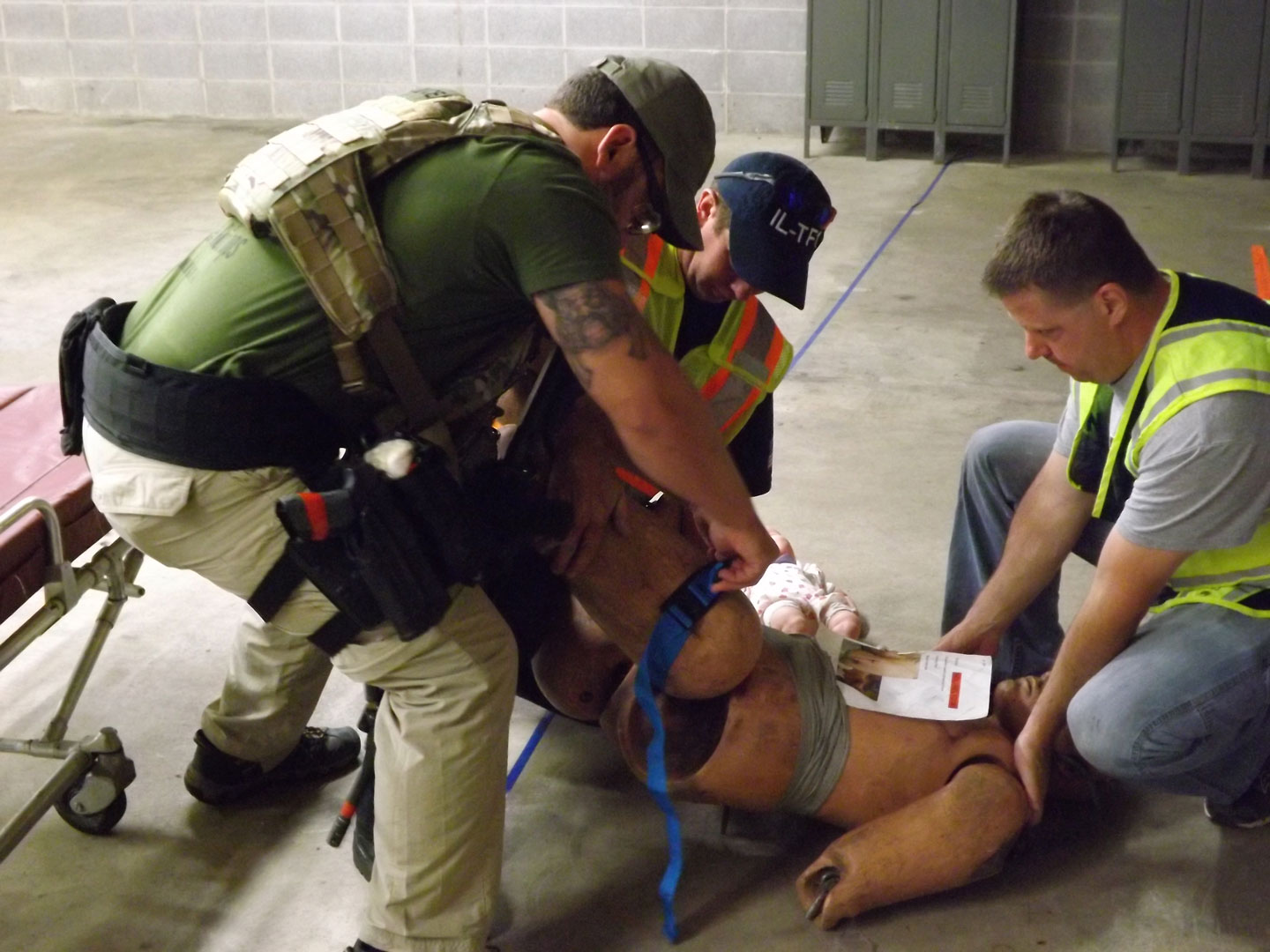 Responders assess and mitigate injuries to a patient before transport.
