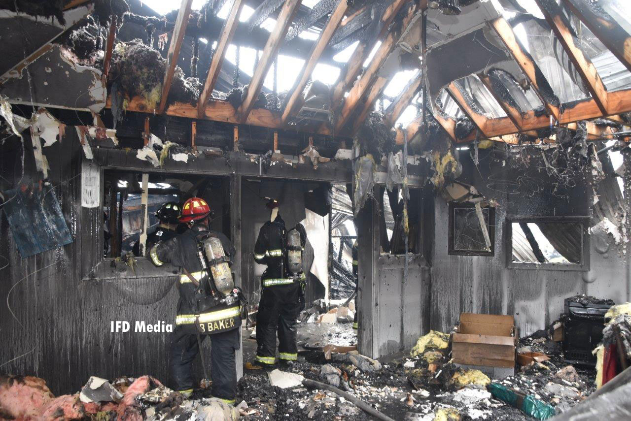 Fire crews perform overhaul in the destroyed warehouse