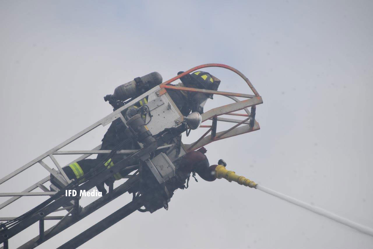 Firefighter on an aerial ladder directing a stream