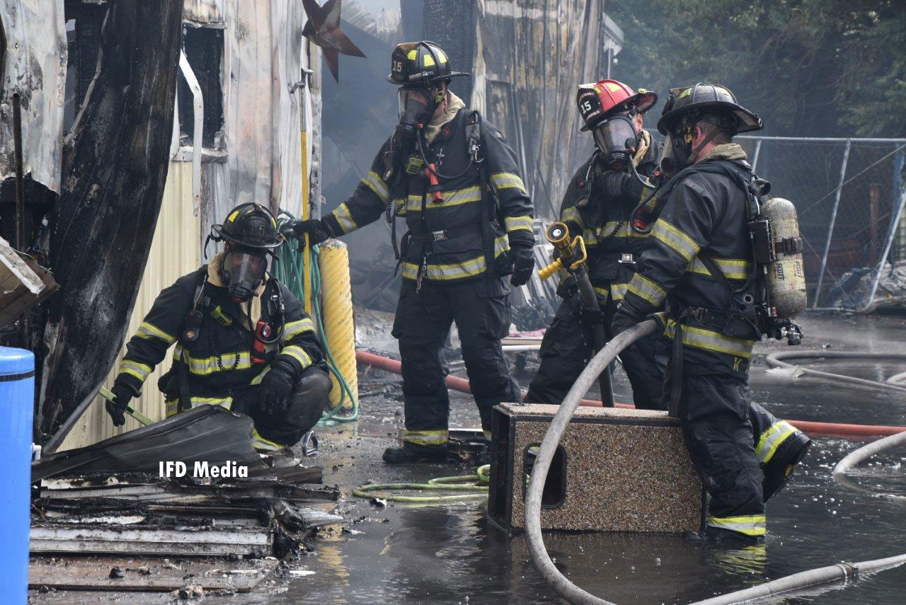 Firefighters with a handline at the scene of the fire