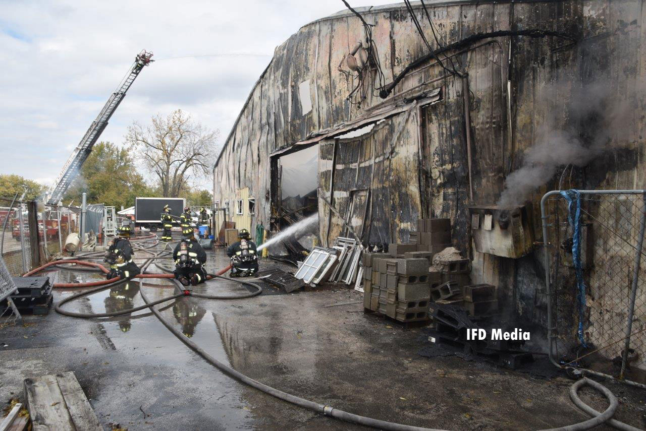 Firefighters operating hose streams on the exterior of the building