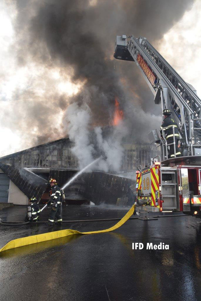 Firefighters put water on the warehouse fire