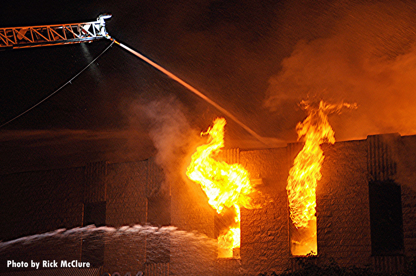Aerial master stream administering water as fire vents from windows