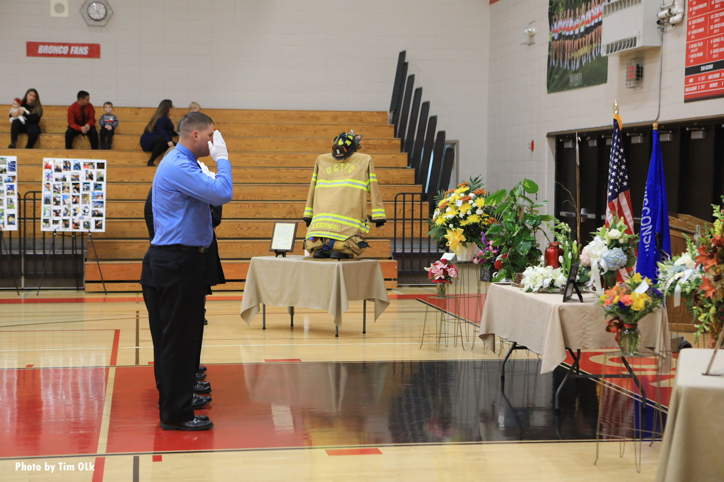 A firefighter salutes his fallen colleague