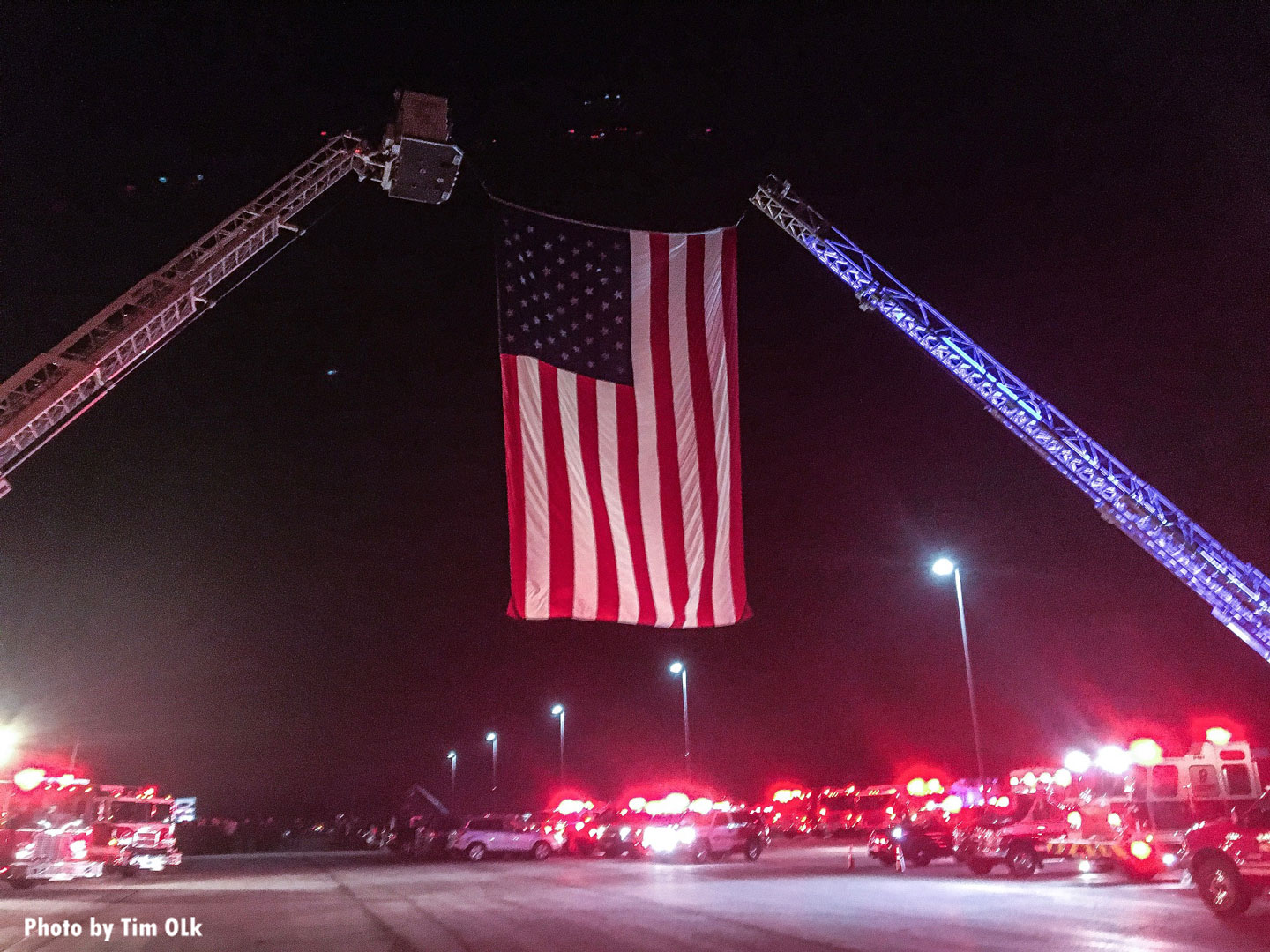 At night, a photo of the flag held between two fire apparatus