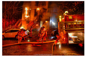 Firefighters pull lines at the scene of the fire in the city of Troy, New York.