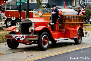 Firefighters drive an old fire truck bearing the remains of Fire Chief William Gitzke.