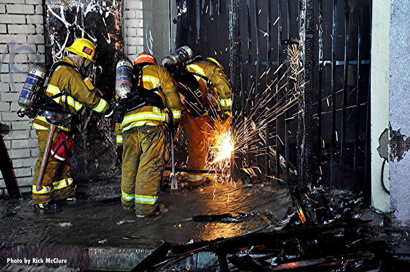 Firefighters use saws to force entry.