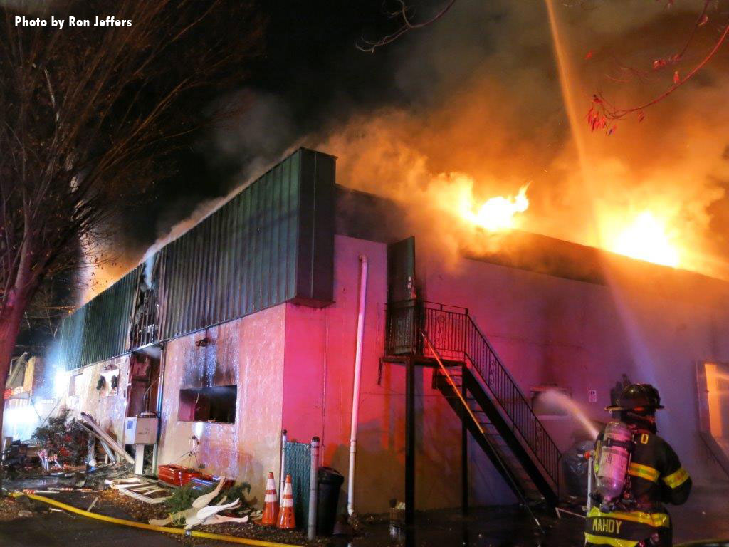Fire burns through the building's roof as firefighters apply water.