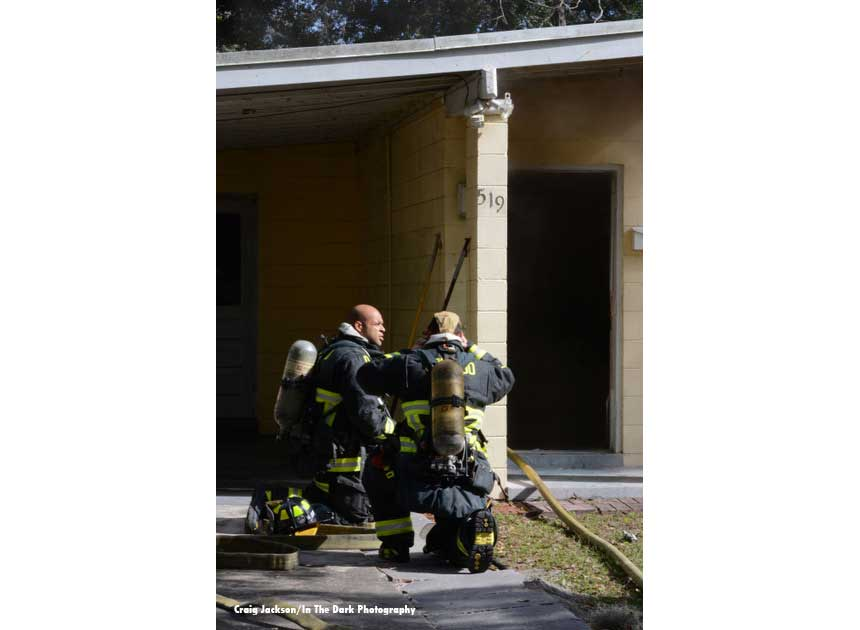 Firefighters with a hoseline outside a house fire