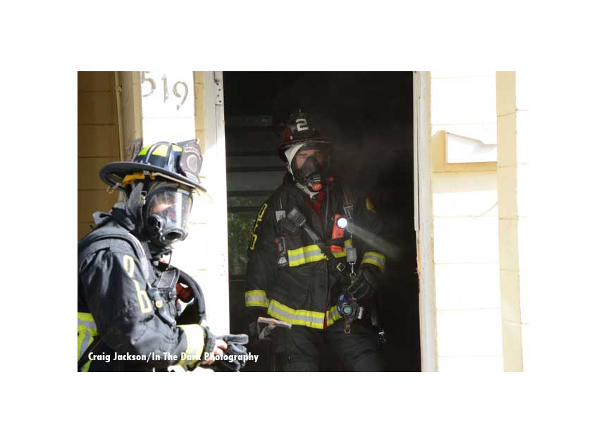 Firefighters in the doorway of a home