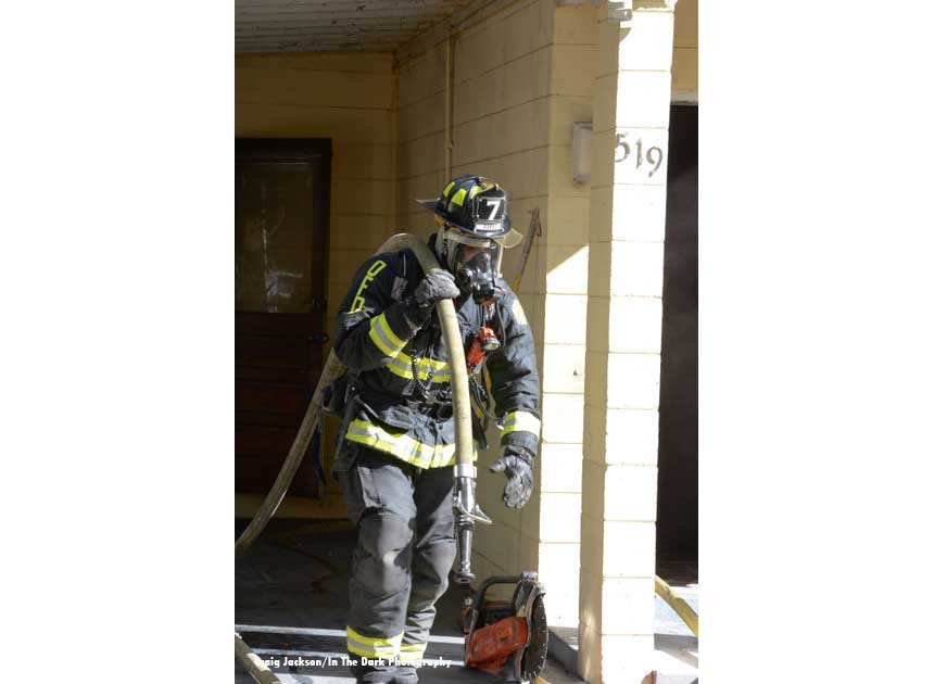 A firefighter hauling hose