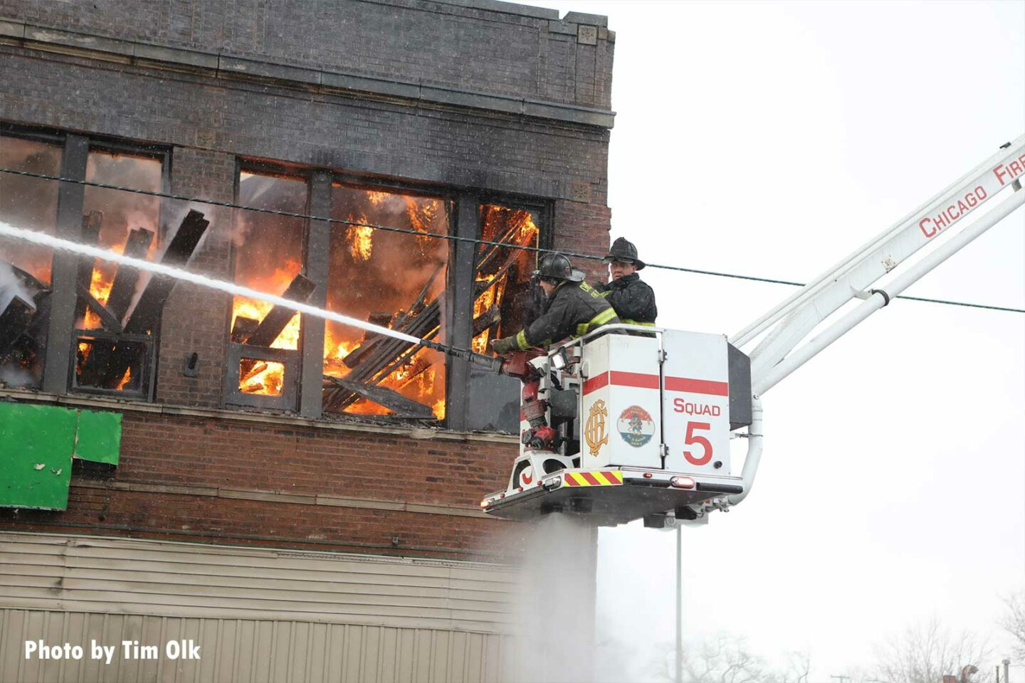 Firefighters in a bucket direct hose streams into the burning church building