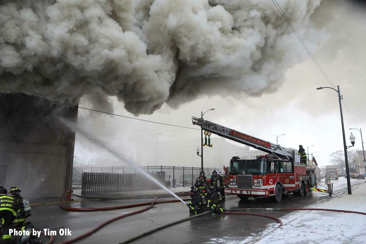 Firefighters direct a hose stream into the building