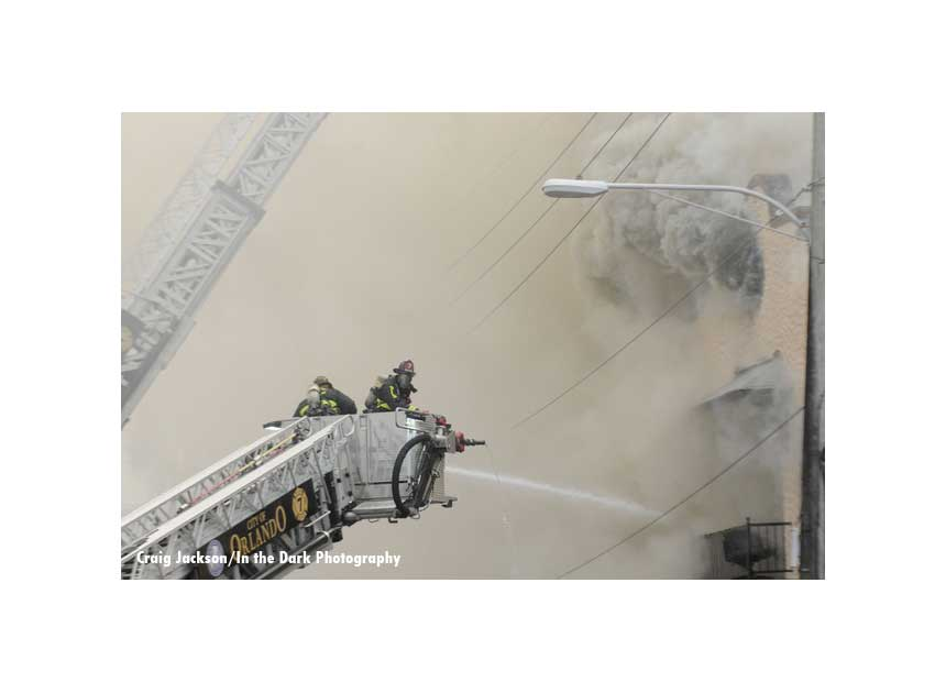 Firefighters in tower ladder buckets battling a major fire in Orlando, Florida.