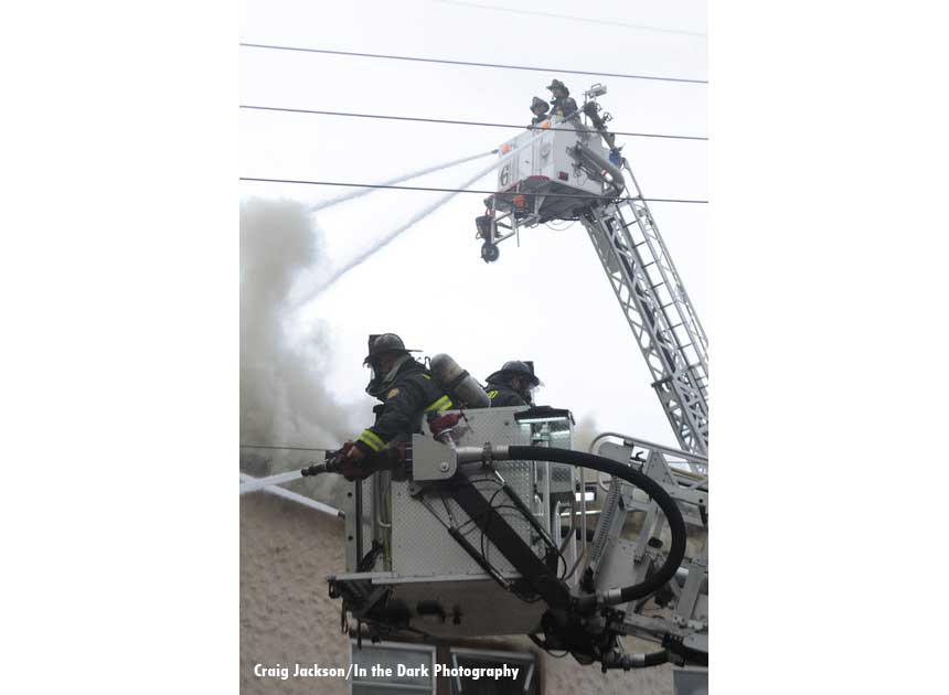 Two tower ladder buckets with firefighters administering streams