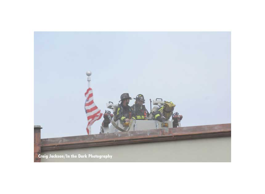 American flag and firefighters in a tower ladder bucket