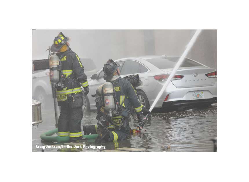 Firefighters direct hose streams from the ground