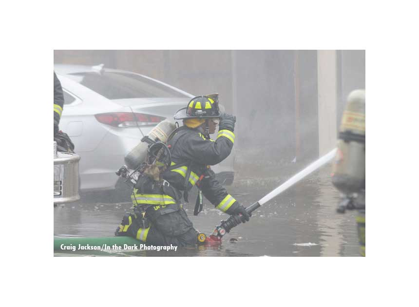 An Orlando firefighter directing a hose stream during fire suppression operations