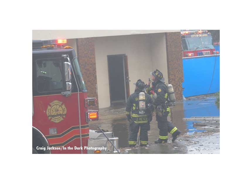 A firefighter directs another firefighter's attention on the fireground