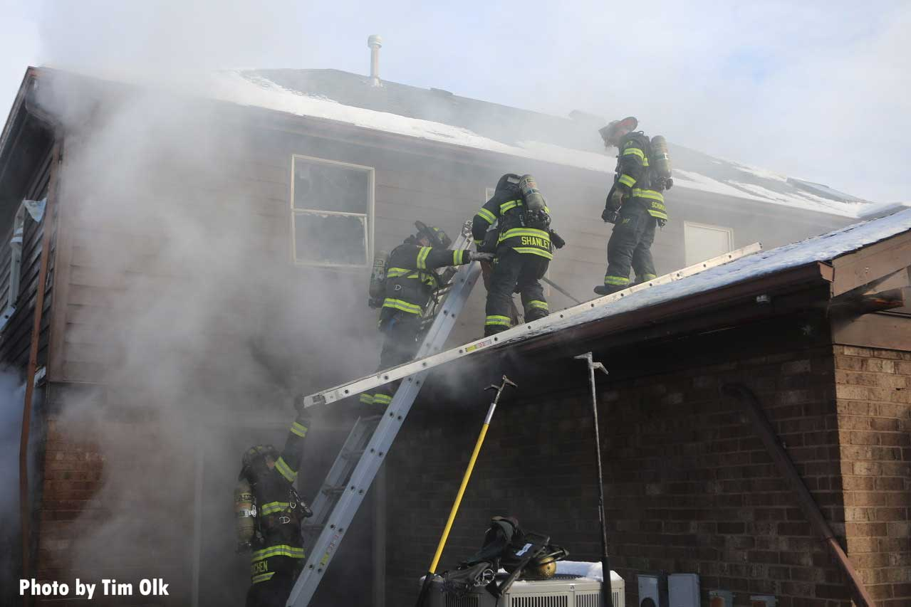 Firefighters ascend a ladder to the roof