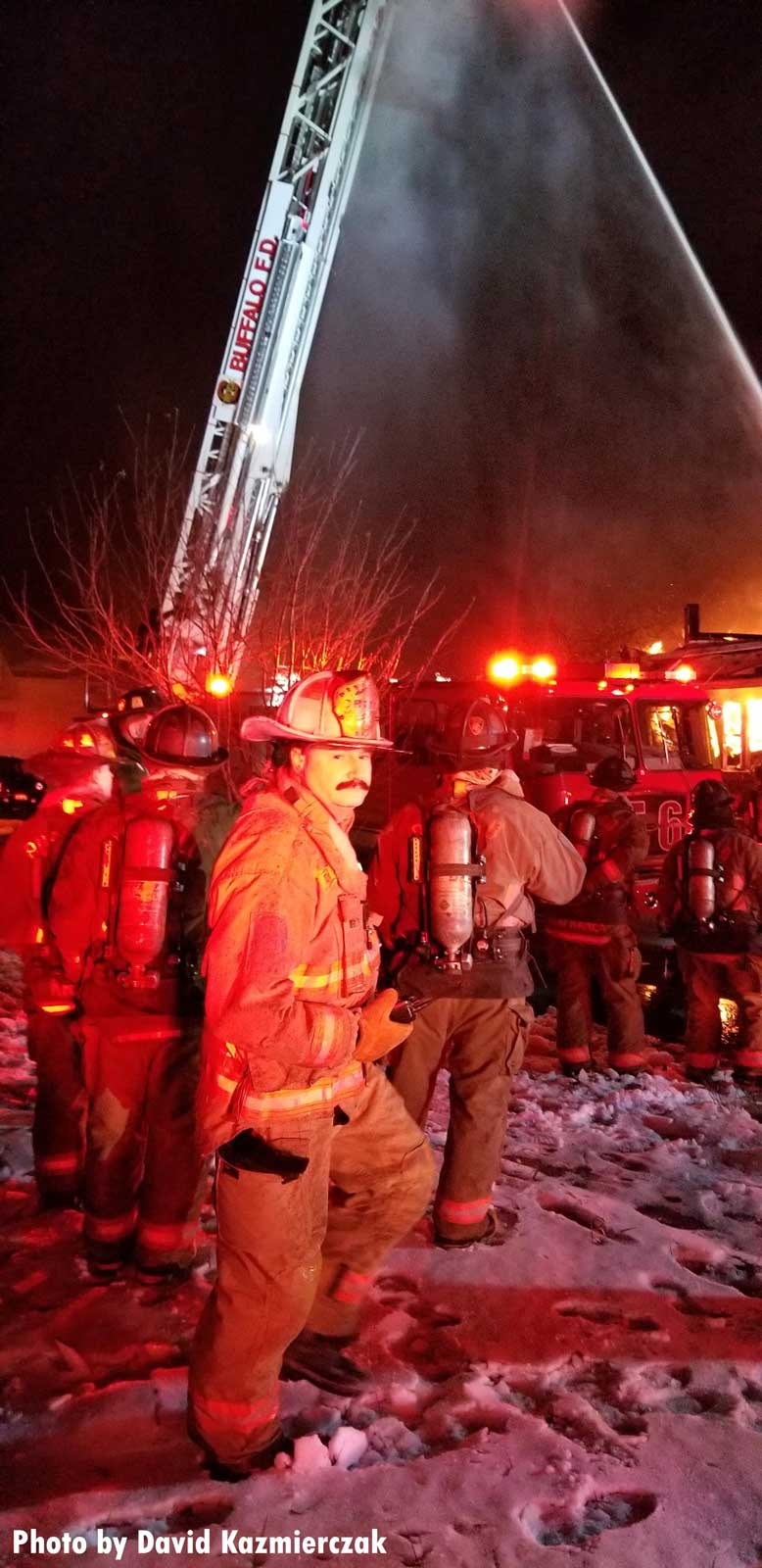 Firefighters and raised aerial device at scene of Buffalo fire