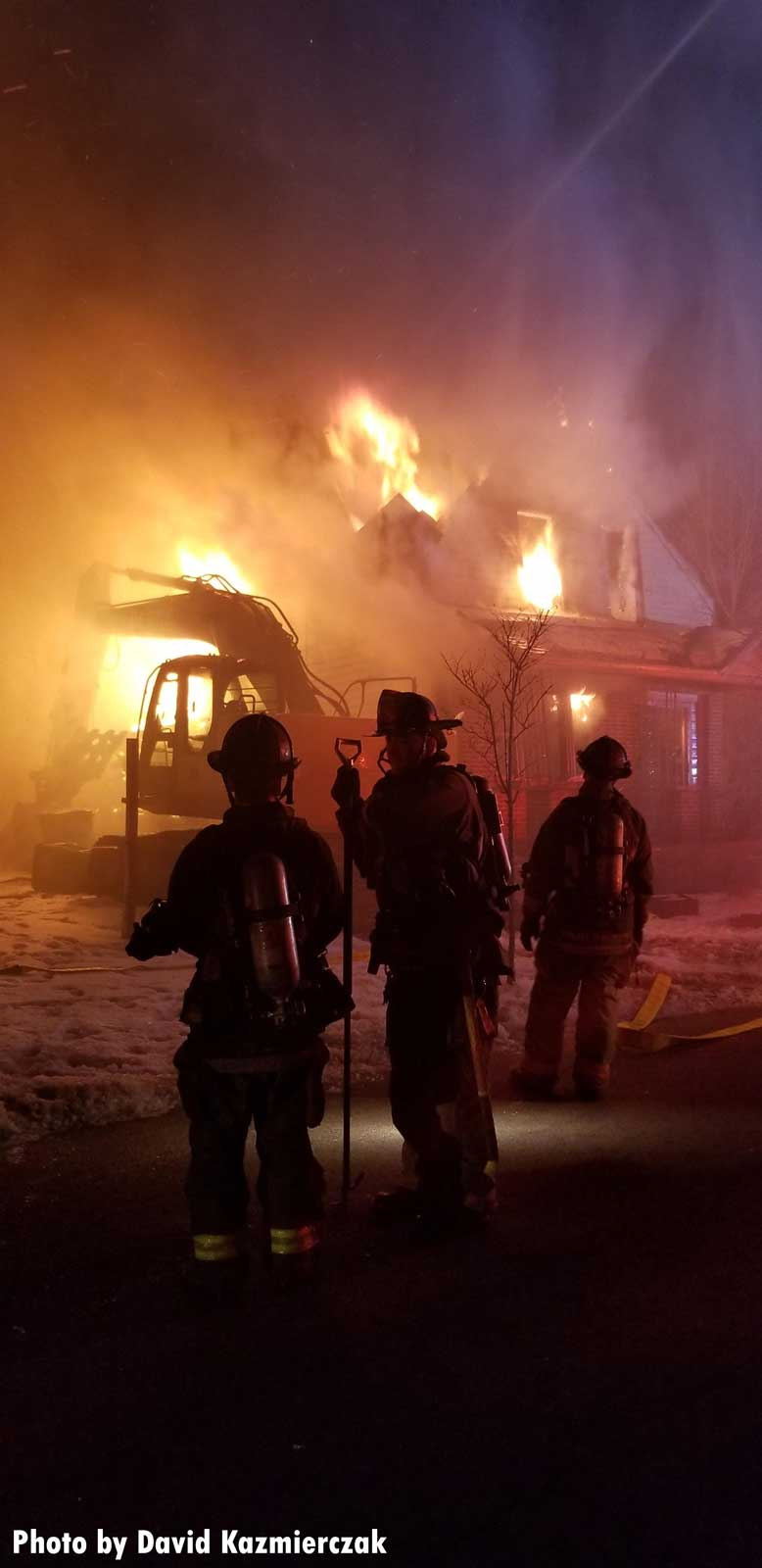 Firefighters on scene as flames from the home seem to impinge on an excavator