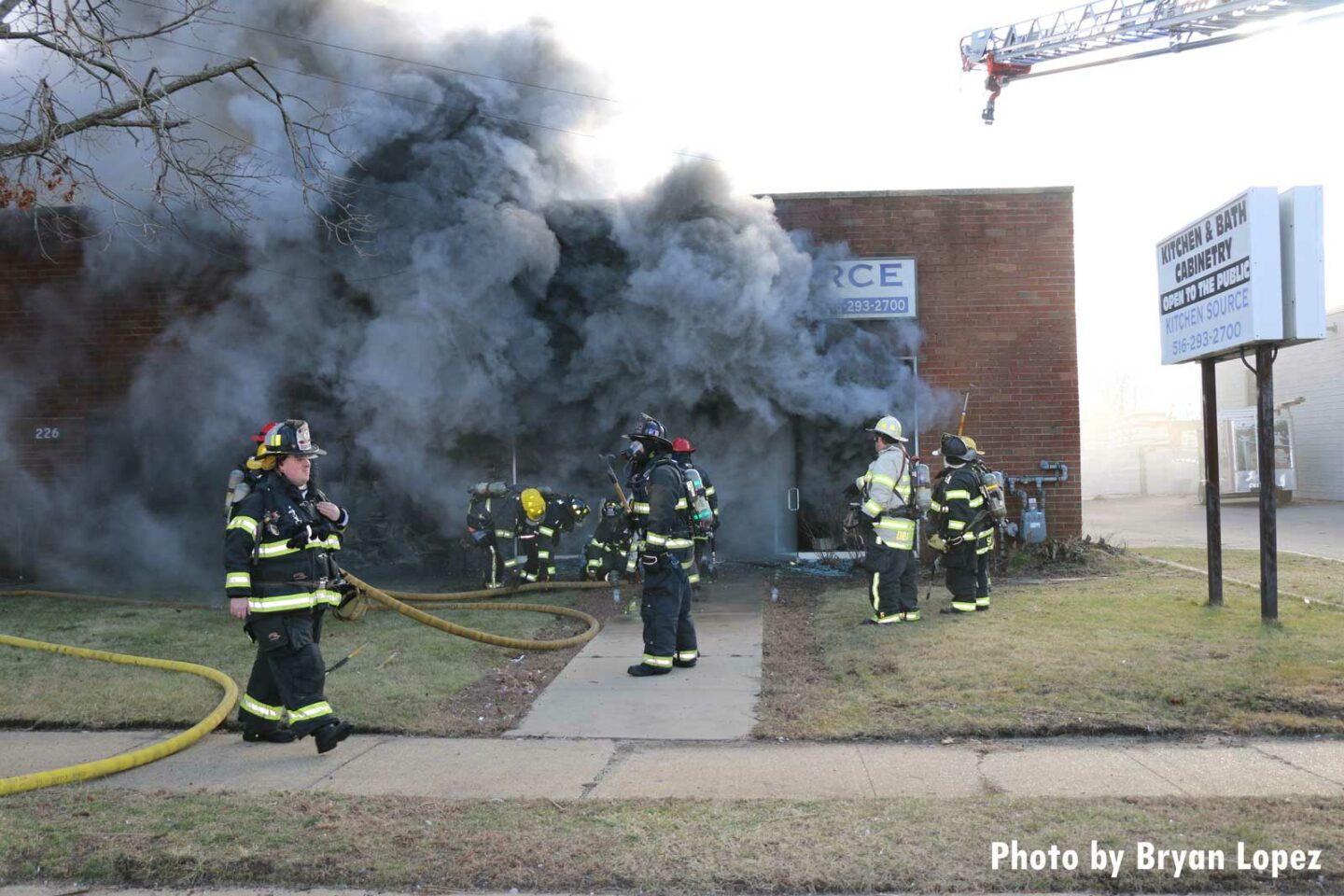 Firefighters with hoselines and smoke condition emanating from building