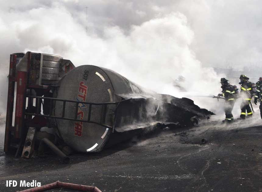 Firefighters train a hoseline on the burning tanker