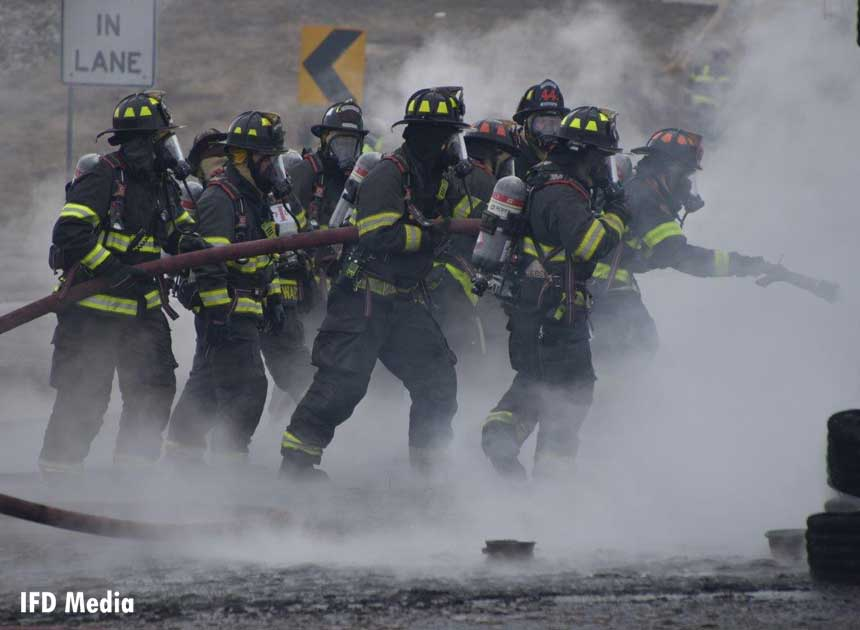 Numerous firefighters advancing a line